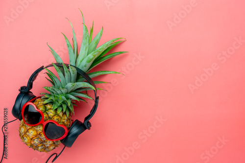 Poster Magasin de musique Table top view aerial image of food for summer holiday season & music background concept.Flat lay object the pineapple listening radio by black headphone for sign of seasonal on modern pink paper.