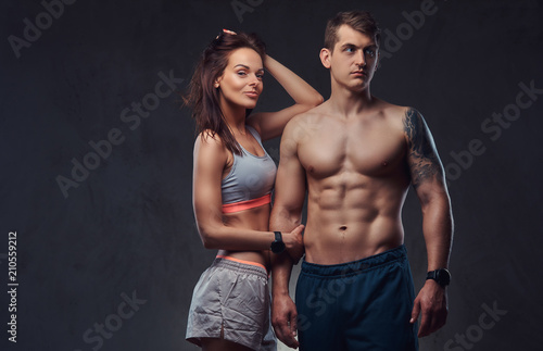 Fotografía  Attractive couple, a slim brunette female wearing sports bra and shorts and handsome shirtless guy cuddling in a studio on a dark textured background
