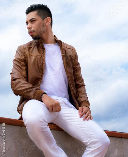 1120b0d183063 Chico joven con chaqueta marron sentado posando - Buy this stock ...
