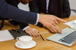 Business people are hand typing on silver color laptop computer put on table