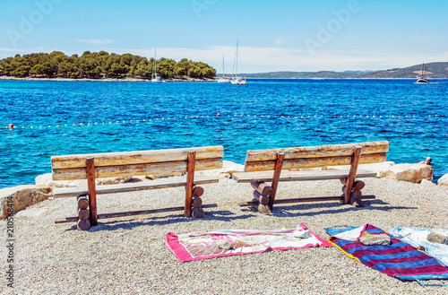 Tela Wooden benches and towels on the beach, Solta