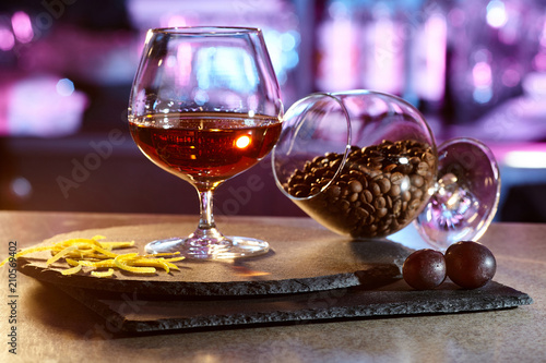 Spoed Foto op Canvas Alcohol A glass of cognac on the bar with decorations of lemon peel.