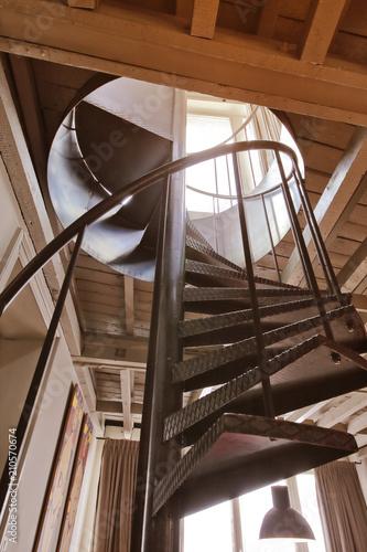 Foto op Canvas Trappen escalier en métal tournant dans rénovation maison ancienne