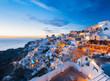 Colorful dramatic light at sunset and the picturesque Oia village, Santorini, Greece. Incredibly romantic sunset on Santorini. Amazing sunset view with white houses.