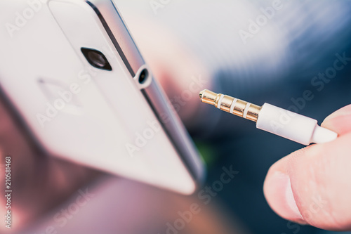 Headphone Jack Of A White Mobile Phone Next To A Headset Cable Wallpaper Mural