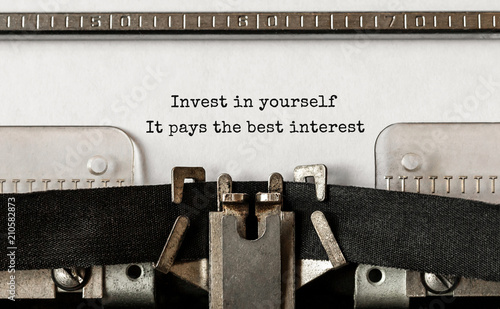 Fotografía  Text Invest in yourself, it pays the best interest typed on retro typewriter