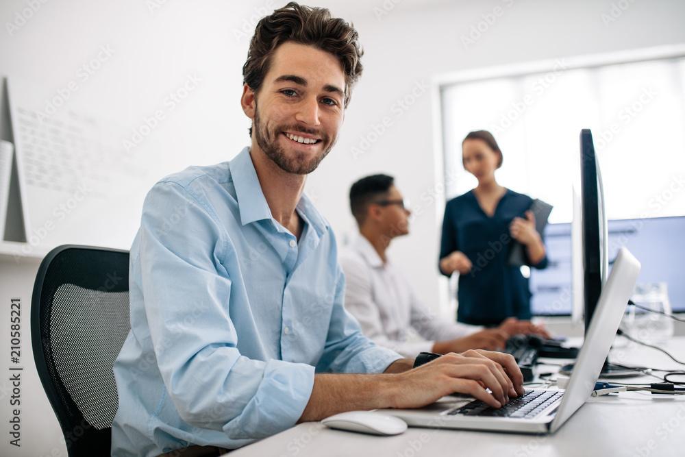 Fototapeta Application developers working on computers in office