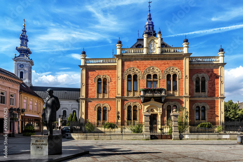 Canvas-taulu Monument of Jovan Jovanovic Zmaj, in front of and neo-classical architecture of Vladicin Court Palace of Bishop in Novi Sad, Serbia