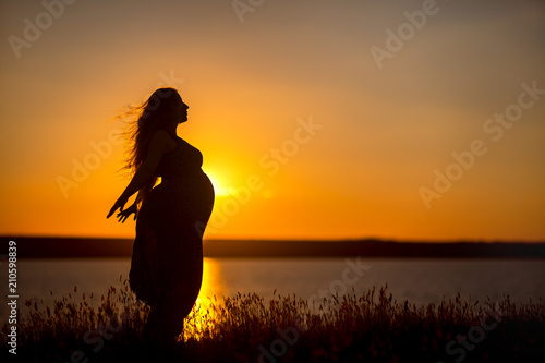 Recess Fitting Zen A pregnant girl against the background of the water at sunset, a woman with long hair and belly spread her hands to the sides and enjoys the freedom of the wind.