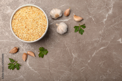 Bulbs, cloves, parsley and bowl with granulated dried garlic on table, top view