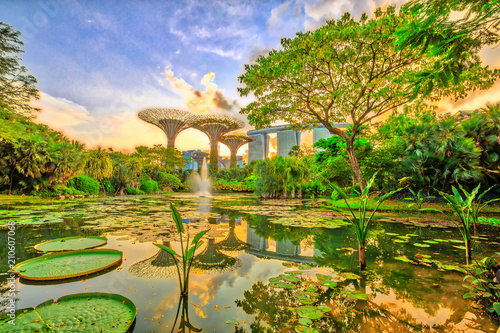 Canvas Print Blue hour skyline of Gardens by the Bay with blue and violet lighting and modern skyscraper reflecting in Water Lily Pond at sunset