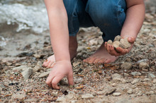 Closeup Of Feet Of Child Playing On The Beach With Stone