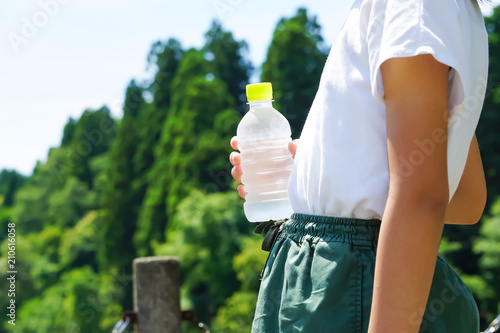 Fotografie, Obraz  A woman holding a bottle of water.  ペットボトルの水を持つ女性