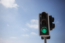 Green Traffic Light.  Blue Sky With Few Clouds Background. Close Up Under View, Copyspace.