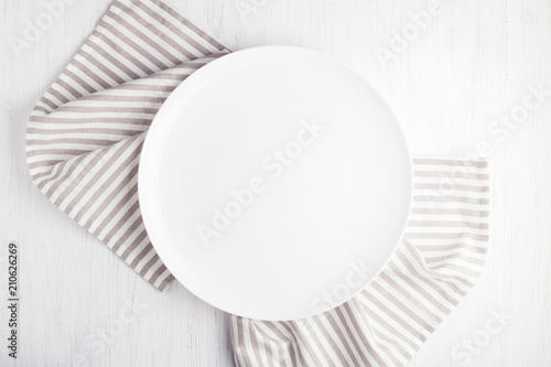Fotografia Empty white circle plate on wooden table with linen napkin