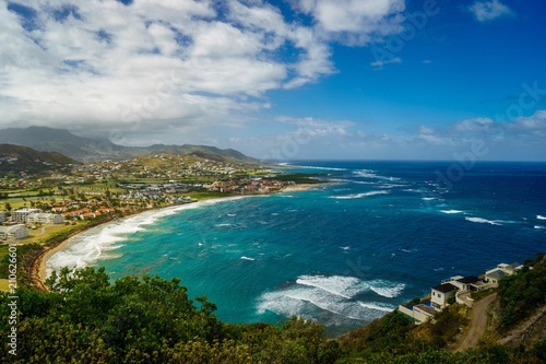 Foto op Plexiglas Caraïben A view over St. Kitts Island with residential area and beaces on the foreground and lush green hills on the background