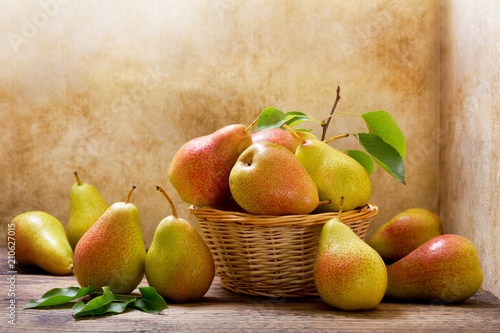 Vászonkép fresh pears with leaves in a basket