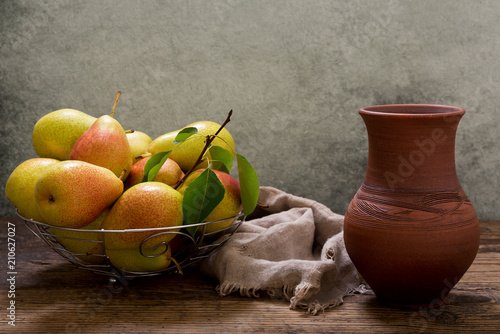 pears with leaves in a basket on wooden table