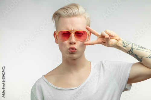 Fotografie, Obraz  Hipster blonde guy wearing trendy pink sun glasses posing pouting and sending air kiss with pouted lips, full of positive emotions and love love