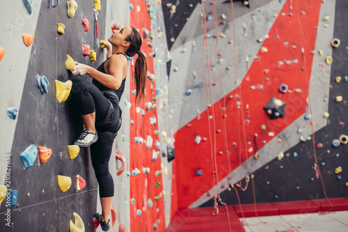 Rear view of sportwoman climber moving up on steep rock, climbing on artificial wall indoors Canvas Print