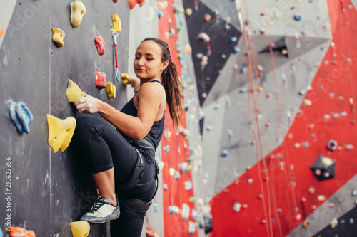 Fototapeta Professional sportwoman climber moving up on steep rock, climbing on artificial wall indoors, side view. Extreme sports and bouldering concept. obraz