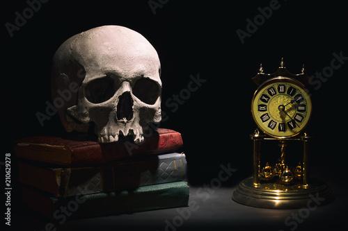 Fotografía Human skull on old books near retro vintage clock on black background under beam of light