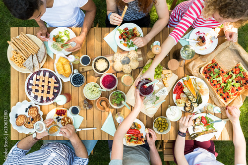 Top view on people eating pizza, pastry and salad during grill party in the garden