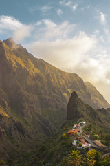 Stunning landscape mountain village in deep canyon with jungle forest on a paradise island. Beautiful golden hour sunrise sunset soft light. Travel photo, postcard. Masca, Tenerife, Canary Islands