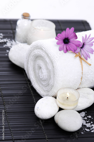 Tuinposter Spa Spa setting with candle, rolled towel , Magnolia , salt, stoneson on mat