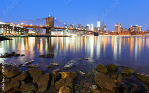 Staande foto New York City Panorama of Brooklyn Bridge, East River and Manhattan at sunset with lights and reflections. New York