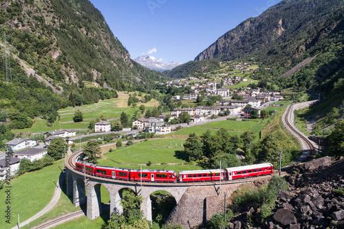 Fotografie, Obraz  Bernina Express, red train of Bernina over the viaduct of Brusio, Unesco heritag