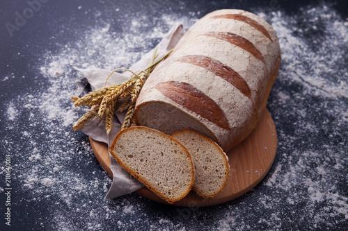 bochenek-chleba-oproszony-maka-na-czarnym-tle