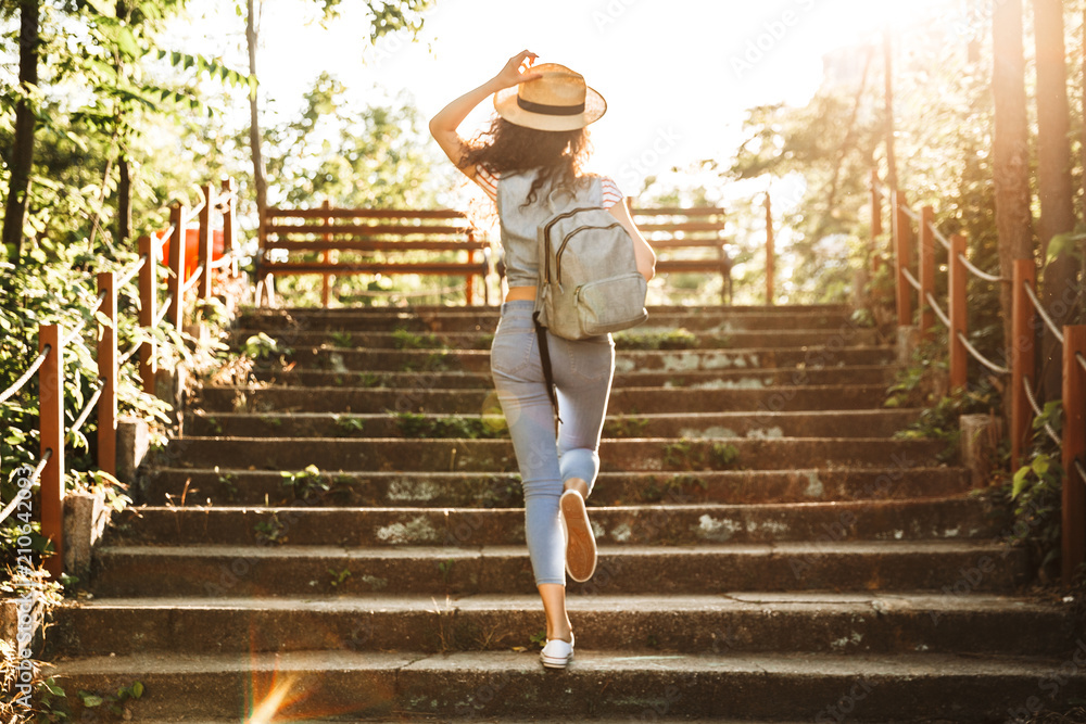 Fototapety, obrazy: Photo from back of young woman 18-20 wearing summer clothes and straw hat, running up stairs in green park on sunny day