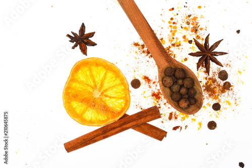 Fototapeta Mulled wine spices kit. Spices kit for preparing mulled wine or hot beverage, close up. Spices kit concept. Spoon with spices, dried orange, cinnamon stick, cardamom and nutmeg on white background obraz