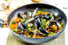 Delicious Seafood Mussels With Red Sauce And Green Onions In A Pan