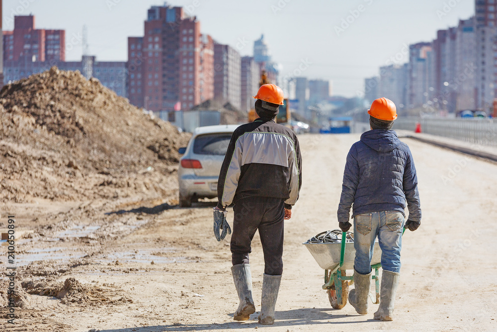 Fototapeta Two workers in helmets drive a wheelbarrow against the background of new buildings.