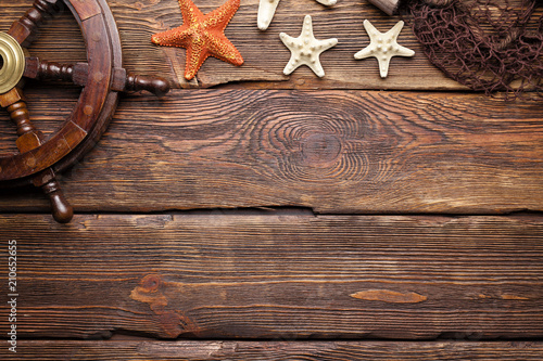 Tuinposter Schip Wooden steering wheel, starfish and fishing net on wooden wall background