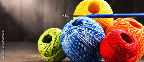 Fotografía Colorful yarn for crocheting and hook on wooden table
