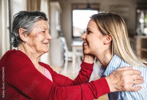 Pinturas sobre lienzo  An elderly grandmother looking at an adult granddaughter at home.