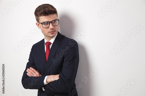 Fototapeta young businessman with glasses and arms folded looks to side obraz na płótnie