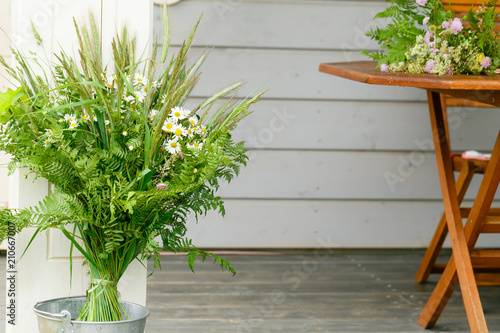 Festive bouquet of white yellow and purple, blue wildflowers, chamomile, herbs and flowers on wooden table, wooden house background. Birthday, Mother's, Women's, Wadding Day concept. Ligo, Latvia