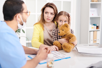 Portrait of worried young mother and cute little girl visiting doctor and talking to pediatrician during consultation