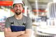 Leinwanddruck Bild - closeup Portrait of a friendly workmen in mechanical engineering //  freundlicher Monteur im Maschinenbau - im hintergrund Fabrikhalle zur Herstellung von Getrieben
