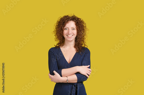 Fototapety, obrazy: Smiling positive female with attractive look, wearing blue dress, posing against yellow blank wall. Happy caucasian woman with red curly hair in positive emotions, looking at camera. People portrait