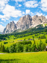 Rocky Ridge Of Pomagagnon Mountain Above Cortina D'Ampezzo With Green Meadows And Blue Sky With White Summer Clouds, Dolomites,, Italy.