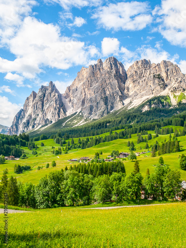Spoed Foto op Canvas Blauwe hemel Rocky ridge of Pomagagnon Mountain above Cortina d'Ampezzo with green meadows and blue sky with white summer clouds, Dolomites,, Italy.