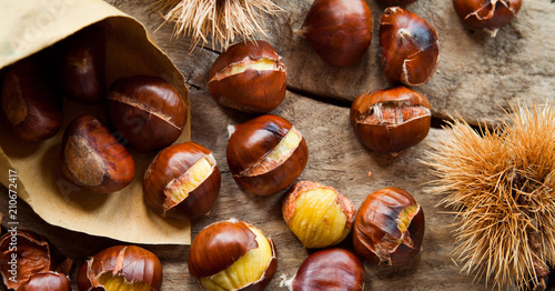 Roasted Sweet Chestnuts nuts on neutral wooden background closeup, macro, detail - healthy seasonal snack.