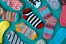 Many Socks Are Scattered On A Turquoise Background. Knitted Socks For Cold Seasons. View From Above.