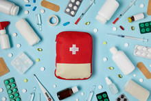 Top View Of Red First Aid Kit Bag On Blue Surface Surrounded With Different Medicines