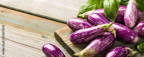 Photo  Heap of small eggplant or aubergine vegetable with basil leaves on old wooden background